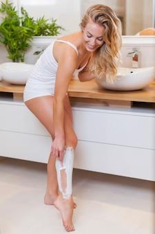 Mulher loira sorridente barbeando as pernas no banheiro