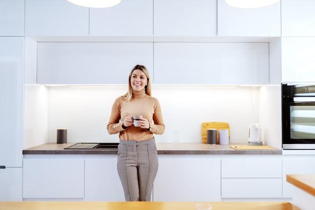 Mulher loira sorridente caucasiana elegante atraente encostado no balcão da cozinha e segurando a caneca com café. interior do apartamento.