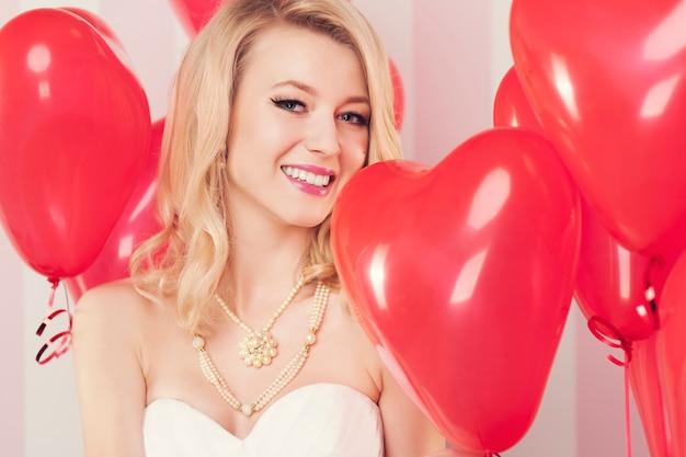 Mulher loira sorridente com balões vermelhos em forma de coração