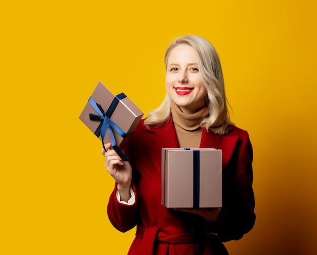 Mulher loira sorridente com casaco vermelho e caixa de presente na parede amarela