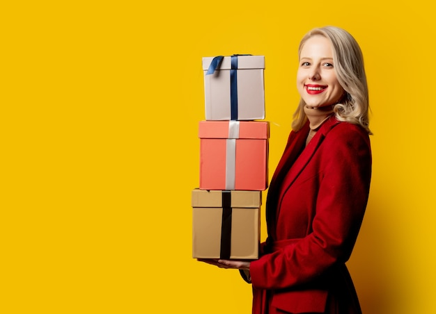 Mulher loira sorridente com casaco vermelho e caixas de presente na parede amarela