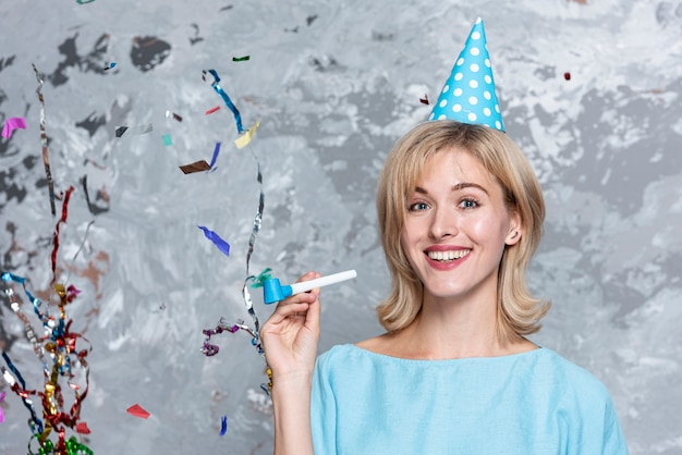 Mulher loira sorridente com chapéu de festa