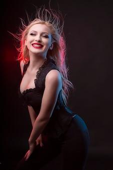 Mulher loira sorridente com espartilho e luz vermelha no estúdio