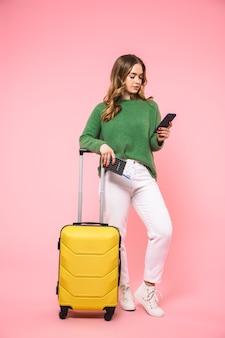 Mulher loira sorridente de corpo inteiro vestindo um suéter verde se preparando para uma viagem enquanto usa o smartphone na parede rosa