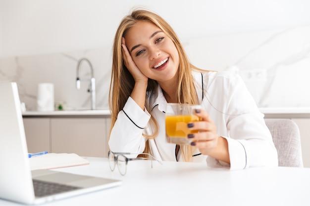 Mulher loira sorridente de pijama, trabalhando com um laptop e bebendo suco enquanto está sentada à mesa na cozinha bem iluminada