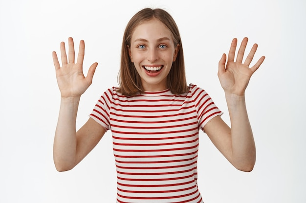 Mulher loira sorridente e feliz acenando com as mãos, diga adeus ou olá, cumprimente ou diga adeus, parecendo amigável e alegre, em pé com uma camiseta listrada sobre uma parede branca