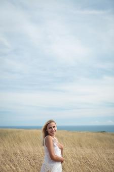 Mulher loira sorridente em pé no campo