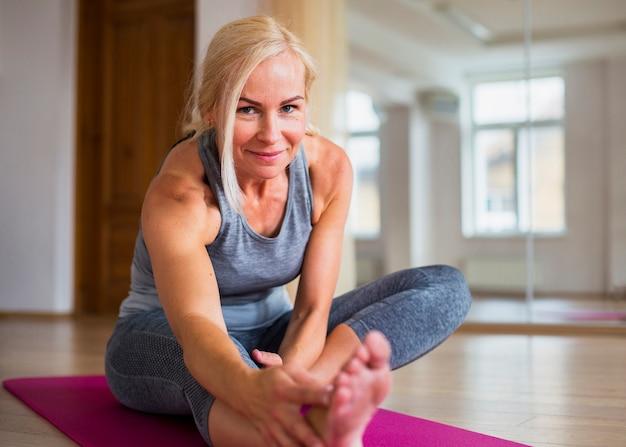 Mulher loira sorridente fazendo pilates