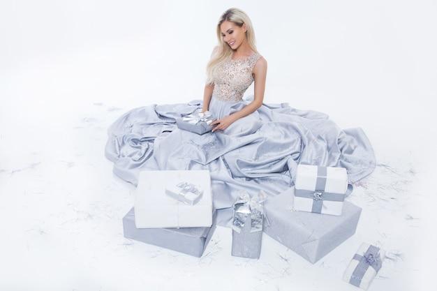 Mulher loira sorridente feliz em vestido longo prateado com caixa de presente e confetes caindo no fundo branco isolado