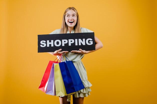 Mulher loira sorridente feliz tem sinal de compras com sacolas coloridas isoladas sobre amarelo