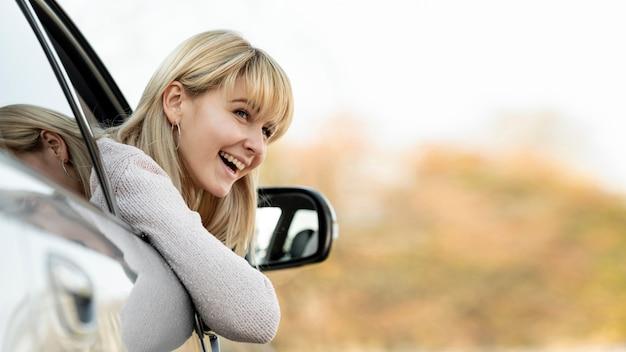 Mulher loira sorridente, levando a cabeça para fora do carro de janela