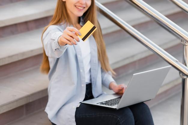 Mulher loira sorridente, mostrando um cartão de crédito