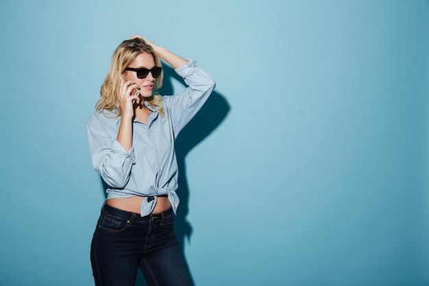 Mulher loira sorridente na camisa e óculos de sol falando pelo smartphone