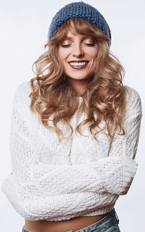 Mulher loira sorridente na camisola e chapéu isolado no branco