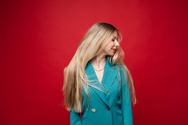 Mulher loira sorridente no casaco azul. isolar em fundo vermelho.