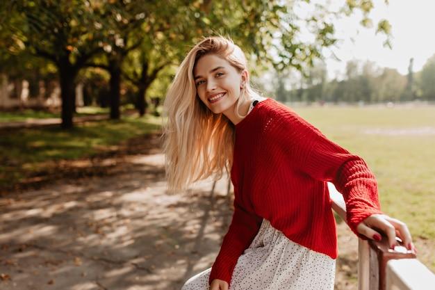 Mulher loira sorridente rindo na rua alegremente. adorável jovem se sentindo feliz no parque outono.
