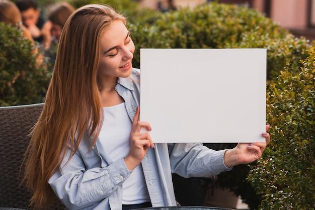 Mulher loira sorridente segurando uma placa de simulação