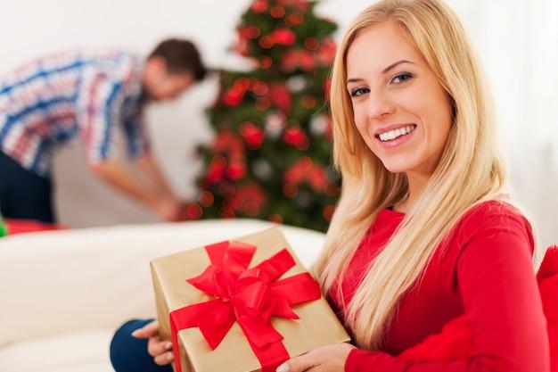 Mulher loira sorridente sentada no sofá na época do natal