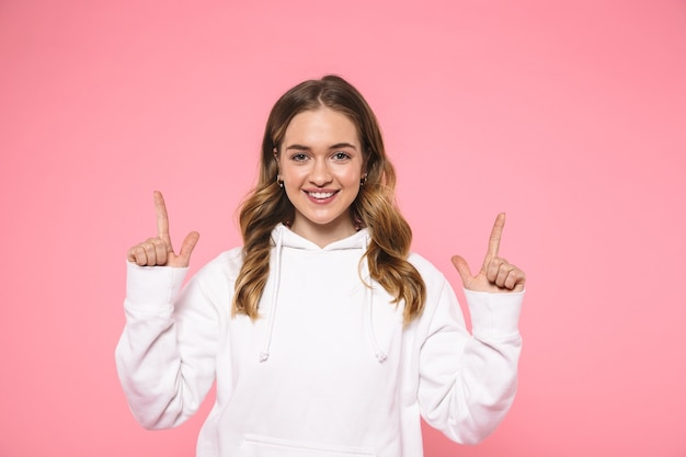 Mulher loira sorridente usando roupas casuais apontando para cima e olhando para a frente sobre a parede rosa