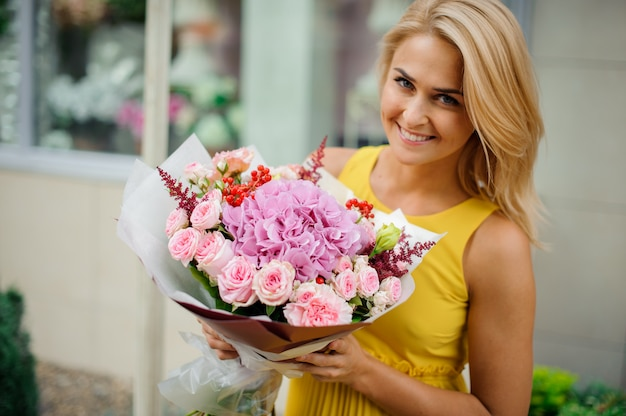 Mulher loira sorridente, vestida com um vestido amarelo, segurando um buquê de flores cor de rosa