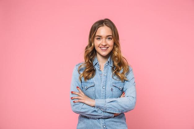 Mulher loira sorridente, vestindo uma camisa jeans, posando com os braços cruzados e olhando para a frente sobre a parede rosa