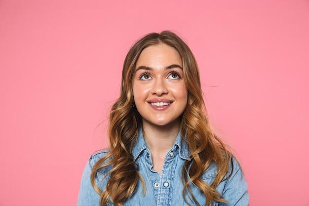 Mulher loira sorridente, vestindo uma camisa jeans, posando e olhando por cima da parede rosa