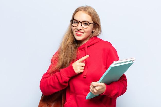 Mulher loira sorrindo alegremente, sentindo-se feliz e apontando para o lado e para cima, mostrando o objeto no espaço da cópia