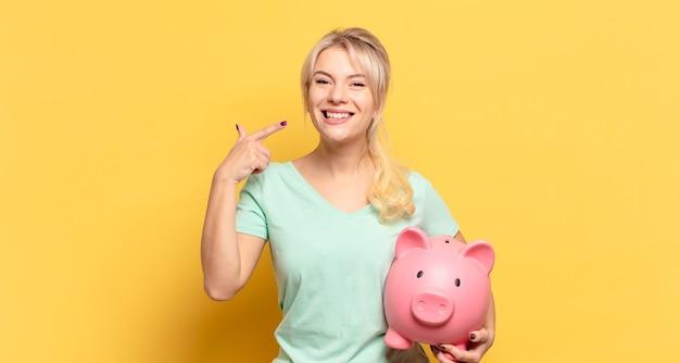 Mulher loira sorrindo com confiança apontando para seu próprio sorriso largo, atitude positiva, relaxada e satisfeita