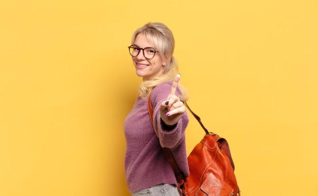 Mulher loira sorrindo com orgulho e confiança fazendo a pose número um triunfantemente, sentindo-se uma líder
