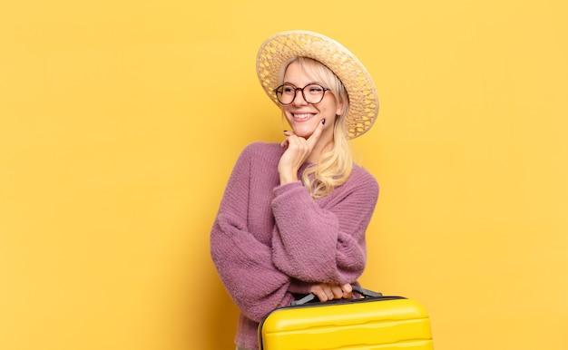 Mulher loira sorrindo com uma expressão feliz e confiante com a mão no queixo, pensando e olhando para o lado
