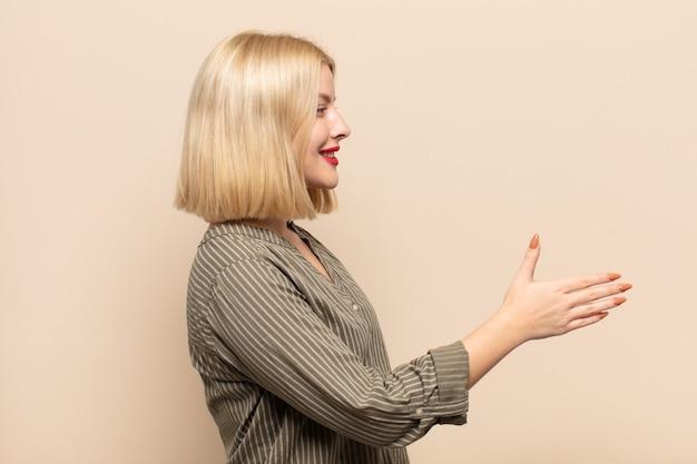 Mulher loira sorrindo, cumprimentando você e dando um aperto de mão para fechar um negócio de sucesso, conceito de cooperação