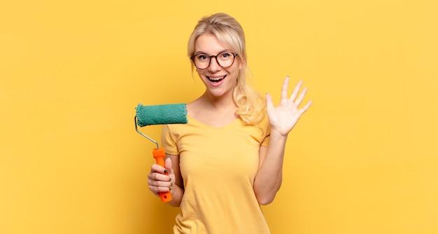 Mulher loira sorrindo e parecendo amigável, mostrando o número cinco ou quinto com a mão para a frente, em contagem regressiva