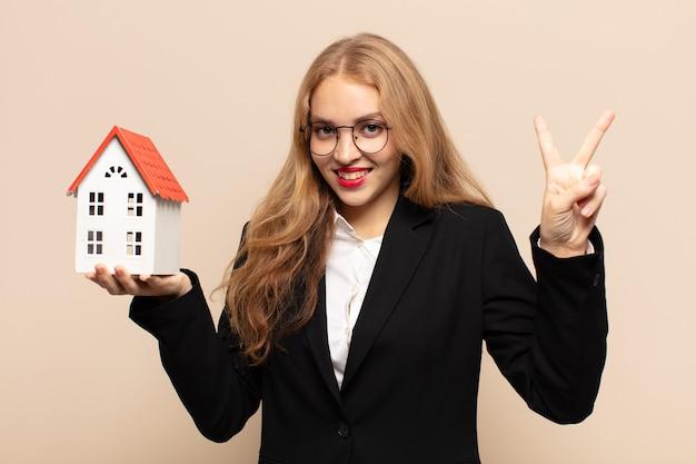 Mulher loira sorrindo e parecendo amigável, mostrando o número dois ou o segundo com a mão para a frente, em contagem regressiva