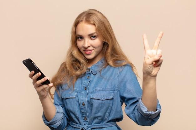 Mulher loira sorrindo e parecendo amigável, mostrando o número dois ou segundo com a mão para a frente, em contagem regressiva