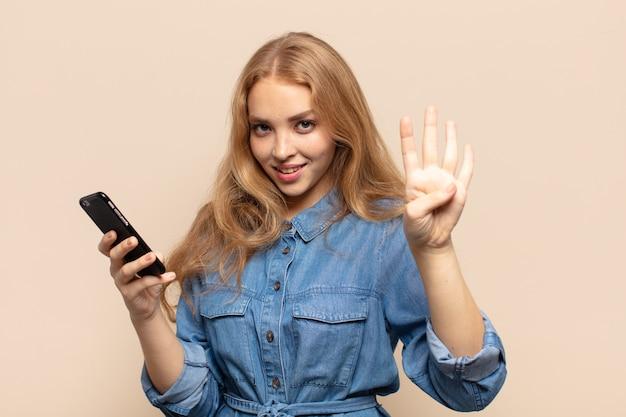 Mulher loira sorrindo e parecendo amigável, mostrando o número quatro ou o quarto com a mão para a frente, em contagem regressiva