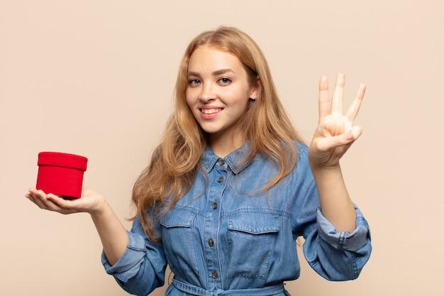 Mulher loira sorrindo e parecendo amigável, mostrando o número três ou terceiro com a mão para a frente, em contagem regressiva