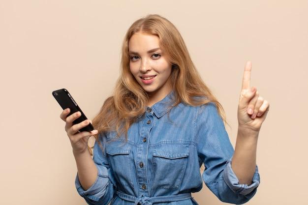 Mulher loira sorrindo e parecendo amigável, mostrando o número um ou primeiro com a mão para a frente, em contagem regressiva Foto Premium