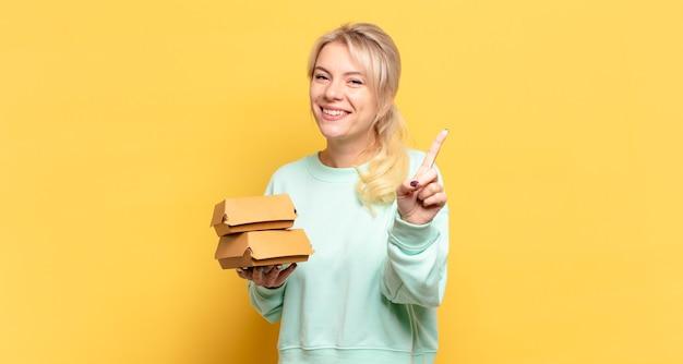 Mulher loira sorrindo e parecendo amigável, mostrando o número um ou primeiro com a mão para a frente, em contagem regressiva