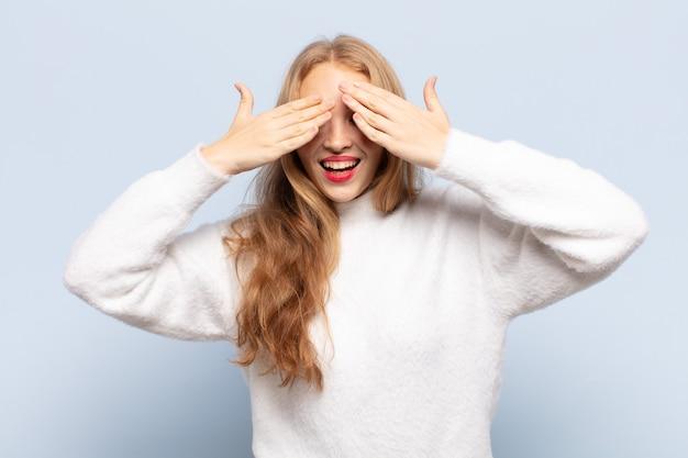 Mulher loira sorrindo e se sentindo feliz, cobrindo os olhos com as duas mãos e esperando por uma surpresa incrível
