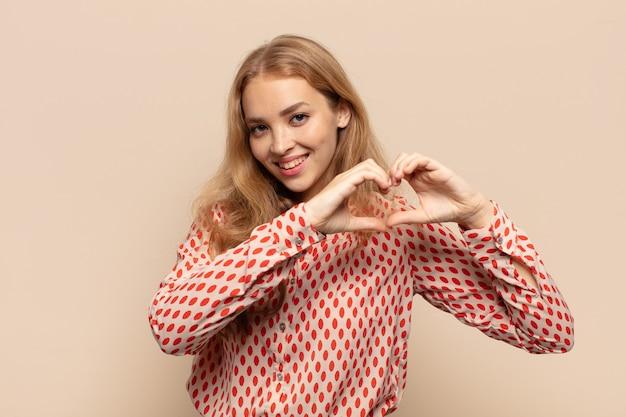 Mulher loira sorrindo e se sentindo feliz, fofa, romântica e apaixonada, fazendo formato de coração com as duas mãos