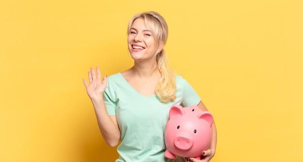 Mulher loira sorrindo feliz e alegre, acenando com a mão, dando as boas-vindas e cumprimentando você ou dizendo adeus