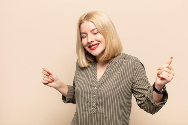 Mulher loira sorrindo, sentindo-se despreocupada, relaxada e feliz, dançando e ouvindo música, se divertindo em uma festa
