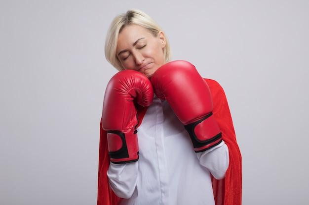 Mulher loira super-heroína de meia-idade com capa vermelha e luvas box, mantendo os punhos sob o queixo franzindo os lábios com os olhos fechados