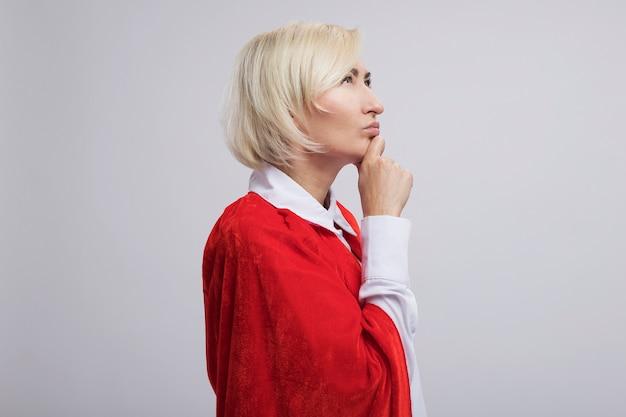Mulher loira super-heroína de meia-idade pensativa com capa vermelha