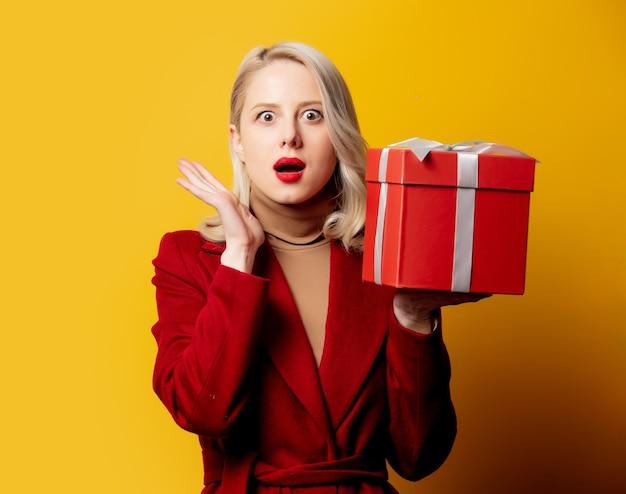 Mulher loira surpresa com casaco vermelho e caixa de presente na parede amarela