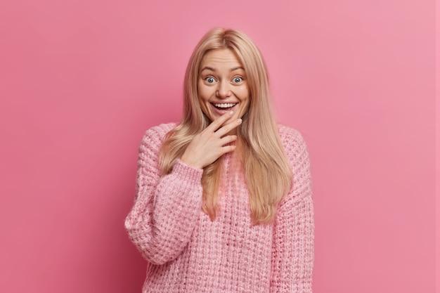 Mulher loira surpresa e divertida encara algo maravilhoso com largo sorriso e perde a fala de espanto vestida com um suéter quente de inverno