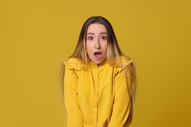 Mulher loira surpresa em fundo amarelo. emoções humanas, expressões faciais.