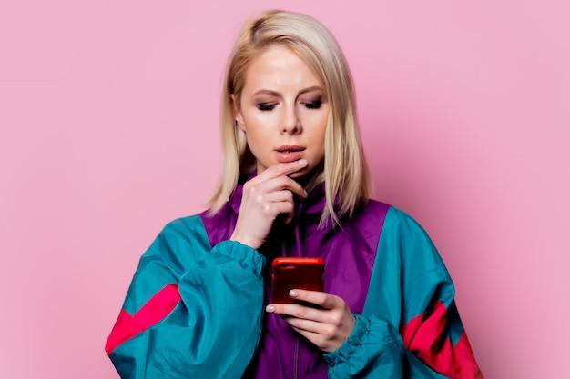 Mulher loira surpresa no esporte terno dos anos 90 na parede rosa