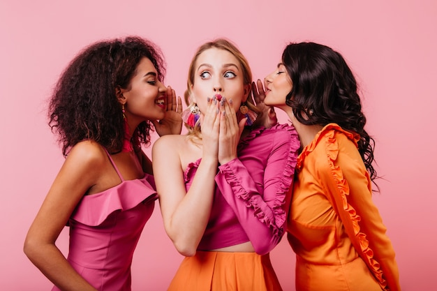 Mulher loira surpresa ouvindo segredos de amigos