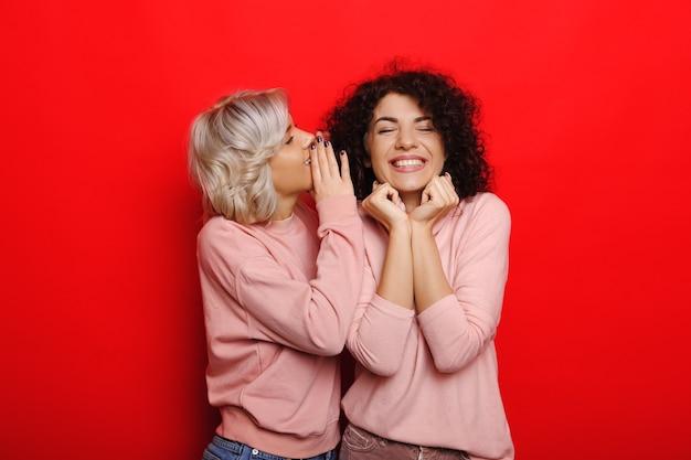 Mulher loira sussurrando algo para sua amiga de cabelos cacheados